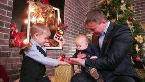 El buen padre pasa Nochebuena con los niños cerca del árbol de navidad, niños descubre un regalo, padre da a metrajes