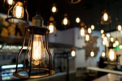 El bulbo de Edison que brillaba intensamente en la oscuridad empañó el fondo Imagen de archivo libre de regalías