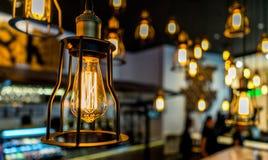El bulbo de Edison que brillaba intensamente en la oscuridad empañó el fondo Imagen de archivo
