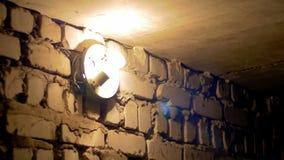 El bulbo del filamento se enciende para arriba en una pared de piedra almacen de video