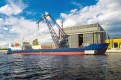 El buque de carga en el puerto y el cargo crane en el embarcadero Fotografía de archivo libre de regalías