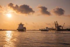 El buque de carga está navegando fuera del puerto en la tarde al mar para transportar el cargo en el envase foto de archivo libre de regalías