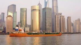 El buque de petróleo está navegando a lo largo del río Huangpu contra la perspectiva de los rascacielos de cristal del centro de  almacen de video
