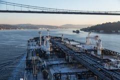 El buque de petróleo está procediendo a través debajo del puente por la mañana Foto de archivo