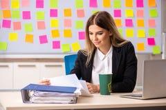 El businesslady hermoso joven en concepto de las prioridades que est? en conflicto imagen de archivo