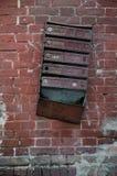 El buzón de entrada soviético viejo en una pared de ladrillo roja Imagenes de archivo