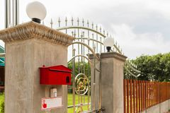 El buzón rojo se cabe al pilar de la cerca de la casa imagen de archivo libre de regalías