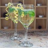 El cóctel del Spritzer con el vino blanco, la menta y el hielo, adornados con ánimo de limón espiral, ajusta Fotografía de archivo