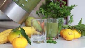 El cóctel verde vertió en los cubiletes de cristal de la licuadora en la cocina metrajes