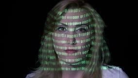 El código binario verde proyectó en la cara de una hembra elegante atractiva del desarrollador de software con el pelo rubio en u almacen de metraje de vídeo