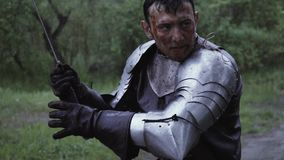 El caballero con la armadura del metal en sus manos está sosteniendo una espada debajo de la lluvia en bosque metrajes