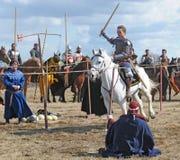 El caballero del caballo con una espada en una mano en un blanco Foto de archivo