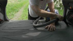 El caballero limpia el tronco del automóvil con la aspiradora con la manguera del aspirador almacen de metraje de vídeo