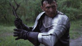 El caballero medieval en el bosque debajo de la lluvia está sacando su espada metrajes