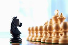 El caballero negro del ajedrez desafía los empeños blancos Imagenes de archivo