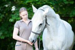 El caballo blanco hermoso trata de la mano joven del ` s del adolescente Foto de archivo