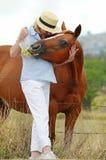 El caballo juguetón del animal doméstico intenta arrebatar el bolso de manzanas del dueño de la mujer Foto de archivo