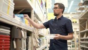 El cabeza de familia está comparando dos cajas plásticas en el supermercado, colocando estantes cercanos metrajes