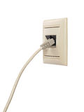 El cable con el conector RJ-45 está conectado con un enchufe de pared Foto de archivo
