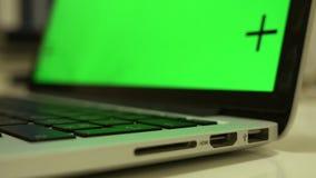 El cable del USB está conectando con una ranura, mano está tapando el cable en un ordenador portátil, cantidad dominante de la cr almacen de metraje de vídeo