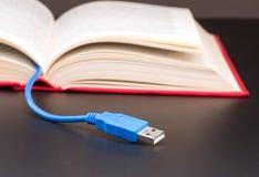 El cable del Usb se pega hacia fuera del libro rojo Imagen de archivo libre de regalías