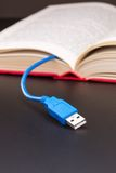 El cable del Usb se pega hacia fuera del libro rojo Imágenes de archivo libres de regalías