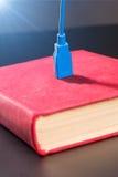 El cable del Usb tapó en un libro Foto de archivo libre de regalías