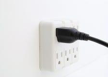 El cable eléctrico tapó en el enchufe de pared. Imagenes de archivo