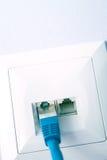 El cable LAN tapó en el enchufe de pared Foto de archivo