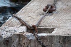 El cable pasa a través de los anillos del metal en el bloque del cemento foto de archivo libre de regalías