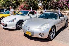 El cabriolé de Pontiac de los deportes y el cabriolé de Nissan 370Z de los deportes están en una exposición de coches viejos en l Fotos de archivo