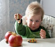 El cabrito agradable de pelo rubio con las manzanas rojas Foto de archivo libre de regalías