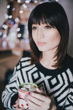 El cacao de la bebida de la mujer con las melcochas delante de Navidad se enciende Fotos de archivo