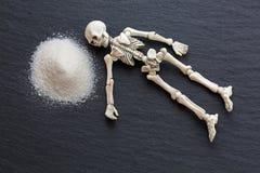 El cadáver esquelético blanco deshuesa la reclinación al lado del blanco peligroso f foto de archivo