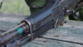 El cadete en uniformes del camuflaje recoge el AK-47 Trenes del soldado almacen de video