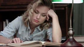 El caer cansada de la mujer joven dormido sobre un libro mientras que se sienta en la tabla después del día largo de trabajo