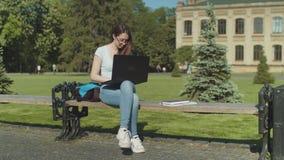 El caer cansada del estudiante dormido con el ordenador port?til en banco almacen de metraje de vídeo