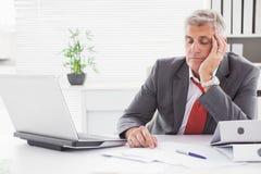 El caer cansada del hombre de negocios dormido en el escritorio imagen de archivo