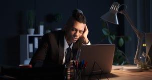 El caer del hombre de negocios dormido mientras que trabaja en el ordenador portátil tarde en noche