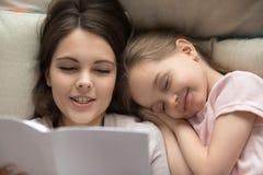 El caer feliz de la niña dormido en libro de lectura de la momia de la cama fotos de archivo