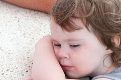 El caer joven linda de la niña pequeña dormido descansando su cabeza en la tabla Fotos de archivo libres de regalías