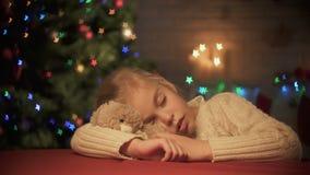 El caer linda de la muchacha dormido en la tabla, abrazando el oso de peluche, centelleo del árbol de Navidad metrajes