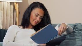 El caer madura cansada de la mujer dormido mientras que lee en casa después de día laborable imagenes de archivo