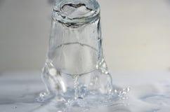 El caer, el volar o colocación de cristal con un líquido claro previsto para la vodka y el chapoteo del líquido imagen de archivo libre de regalías