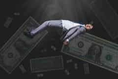 El caer y hombre de negocios uncouncious en desgaste formal con el billete de banco Foto de archivo