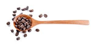El café asado, woden la cuchara en el fondo blanco Foto de archivo libre de regalías