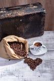 El café caliente con los granos de café se derramó fuera del bolso en la forma Fotografía de archivo