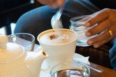 El café caliente puso un vidrio de blanco con una rotura casual del trabajo imagenes de archivo