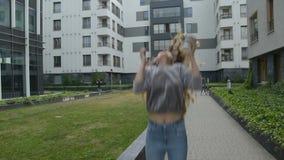 El café de consumición de la muchacha y acaba de ganar un premio enorme Ella está bailando y salto Mujer joven emocionada feliz q metrajes