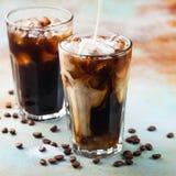 El café de hielo en un vidrio alto con crema vertió encima y los granos de café Bebida fría del verano en un fondo oxidado azul Fotografía de archivo libre de regalías